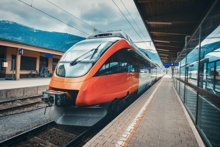 High speed train on the railway station in mountains at sunset