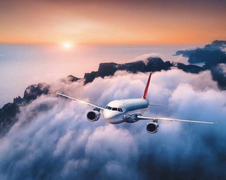 Passenger airplane is flying over clouds at sunset